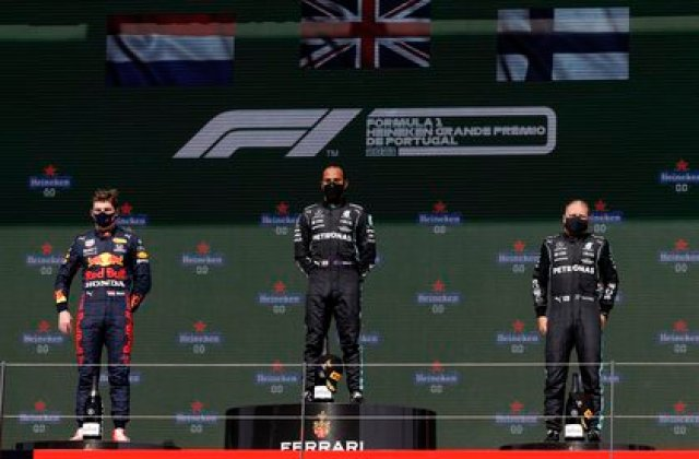Formula One F1 - Portuguese Grand Prix - Algarve International Circuit - Portimao, Portugal - May 2, 2021 Mercedes' Lewis Hamilton on the podium after winning the race alongside second place Red Bull's Max Verstappen and third place Mercedes' Valtteri Bottas REUTERS/Juan Medina