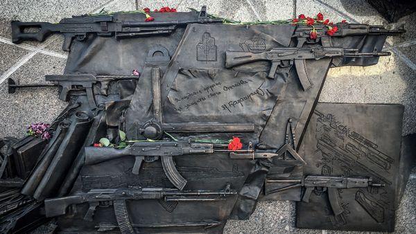 Diferentes representaciones del AK-47 esculpidas en metal, incluyendo la errónea, el grabado abajo a la derecha (AFP)