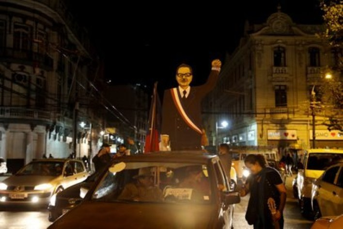 A cardboard figure depicting former Chilean President Salvador Allende is seen on the roof of a car after people voted during a referendum on a new Chilean constitution, in Valparaiso, Chile. REUTERS/Rodrigo Garrido