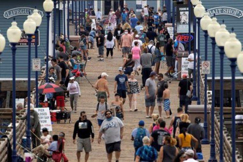 FOTO DE ARCHIVO: Pocas personas usan mascarillas mientras caminan por el muelle de la playa durante el brote de coronavirus en Oceanside, California, EEUU. 22 de junio de 2020. REUTERS/Mike Blake/File Photo