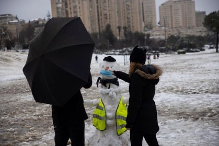 People play with snow in a park on a snowy morning in Jerusalem, February 18, 2021. REUTERS / Ronen Zvulun