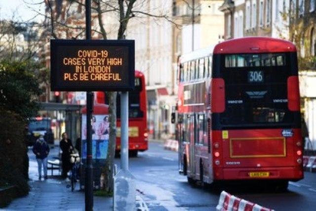 Los autobuses pasan un cartel con un mensaje de información sobre la salud pública, en medio de la propagación de la enfermedad del coronavirus (COVID-19), a medida que entran en vigor nuevas restricciones, en Londres, Gran Bretaña, el 20 de diciembre de 2020. REUTERS/Toby Melville