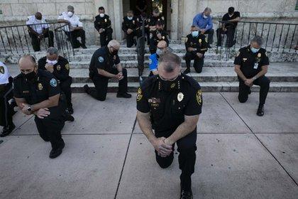 Policías se arrodillan en un gesto de apoyo a la manifestación contra la violencia policial en Coral Gables, Florida (30 de mayo)