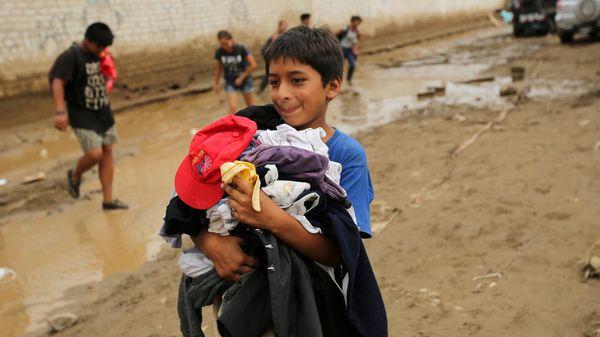 Un niño carga ropa que recibió como donativo luego de ser damnificado ante las graves inundaciones (Reuters)