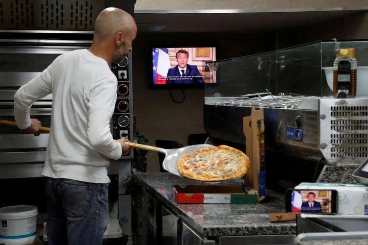 El presidente francés Emmanuel Macron se dirige a la nación sobre el brote del coronavirus, en una pantalla de televisión en una pizzería para llevar en Niza, Francia (Reuters)
