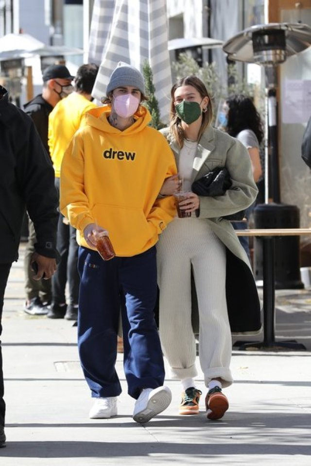 Photo © 2021 Backgrid/The Grosby Group Beverly Hills, February 20, 2021. Justin and Hailey Bieber step out for a late breakfast at Croft Alley in Beverly Hills wearing cozy outfits for a chill Saturday morning. The 26 year old singer kept things casual in a bright yellow Drew House hoodie paired with blue sweat pants and white trainers. While his 24 year old model wife was equally casual in a long grey coat over a cream knit outfit and orange Nike trainers.