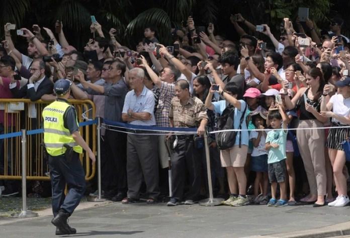 Ciudadanos de Singapur observan el paso del auto de Donald Trump (AP Photo/Joseph Nair)