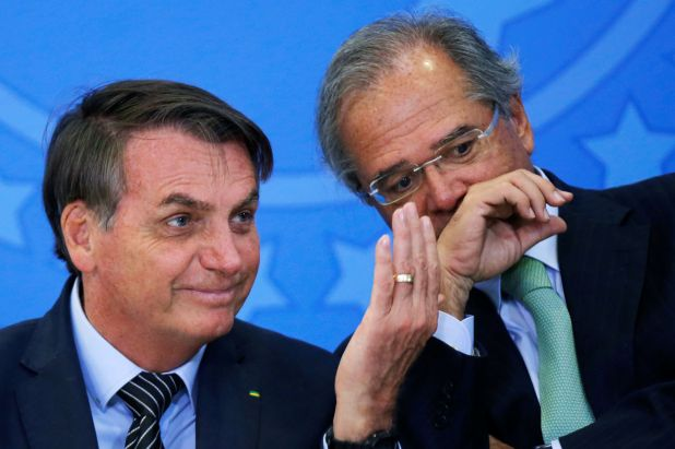 Brazil's President Jair Bolsonaro gestures next to Brazil's Economy Minister Paulo Guedes during a launch ceremony of real estate credit incentive program of the Caixa Economica Federal Bank at the Planalto Palace in Brasilia, Brazil Fabruary 20, 2020. REUTERS/Adriano Machado
