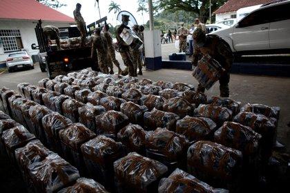 Unidades del Servicio Nacional Aeronaval de Panamá cargan bultos con 2,969 paquetes con presunta cocaína (EFE/Bienvenido Velasco)