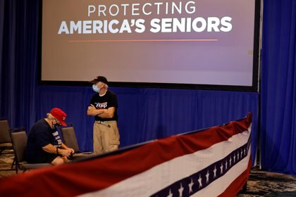 """Foto del evento en el que Trump realizó el anuncio. En la pared, una pantalla transmite la frase """"protegiendo a los adultos mayores de Estados Unidos"""". Foto: REUTERS/Carlos Barria"""