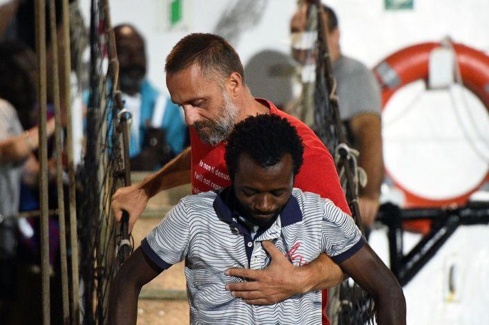 Un hombre recibe ayuda en el barco de rescate español Open Arms NGOtras su llegada a Lampedusa (REUTERS/Guglielmo Mangiapane)