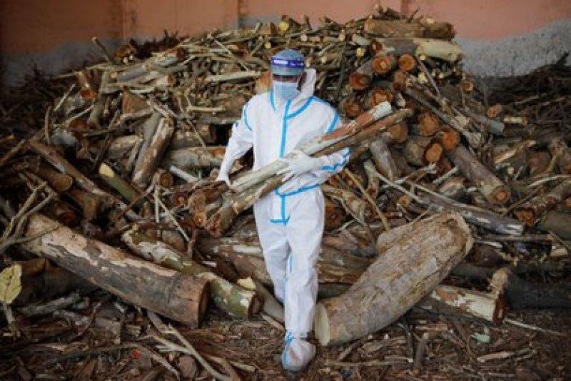 Un hombre con un equipo de protección individual (EPI) transporta madera para prearar una pira funeraria para fallecidos por la COVID-19 en un crematorio en Nueva Dehli, la India, el 26 de abril de 2021. REUTERS/Adnan Abidi