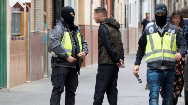 Dos agentes de la Policía Nacional caminan y hablan con algunas personas durante el registro de la casa en la que vivía el presunto yihadista en Sevilla, en abril (EFE)