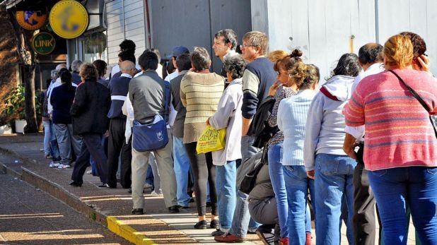 Beneficiarios de las ayudas estatales hacen fila frente a los bancos para percibir los subsidios de emergencia