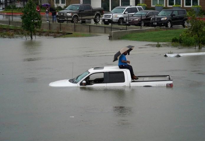 Un hombre se sienta en la parte superior de su camioneta en un camino inundado de Houston, el jueves 19 de septiembre de 2019. (Melissa Phillip/Houston Chronicle via AP)