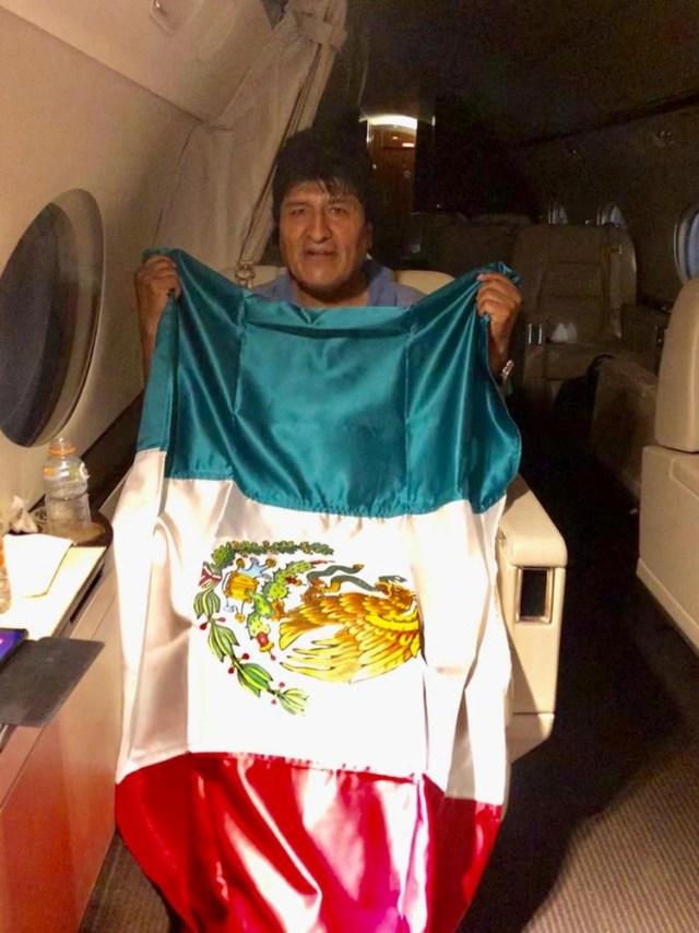 Evo Morales dentro del avión con una bandera de México (Reuters)