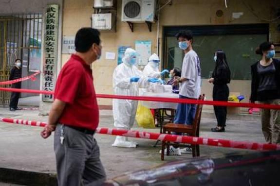 Trabajadores sanitarios en trajes de protección realizan pruebas de ácido nucleico a los residentes de un complejo residencial en Wuhan, la ciudad china más afectada por el brote de la enfermedad coronavirus (COVID-19), en la provincia de Hubei, China, el 15 de mayo de 2020. REUTERS