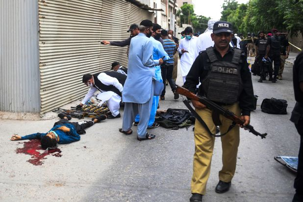 EDITORS NOTE: Graphic content / Policemen gather around the body of an alleged gunman outside the Pakistan Stock Exchange building in Karachi on June 29, 2020. - Gunmen attacked the Pakistan Stock Exchange in Karachi on June 29, with four of the assailants killed, police said. (Photo by Asif HASSAN / AFP)