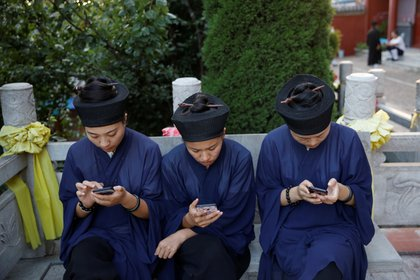 Monjes taoistas en el templo de Jiuyang, en Jinan, China, miran sus celulares REUTERS/Tingshu Wang