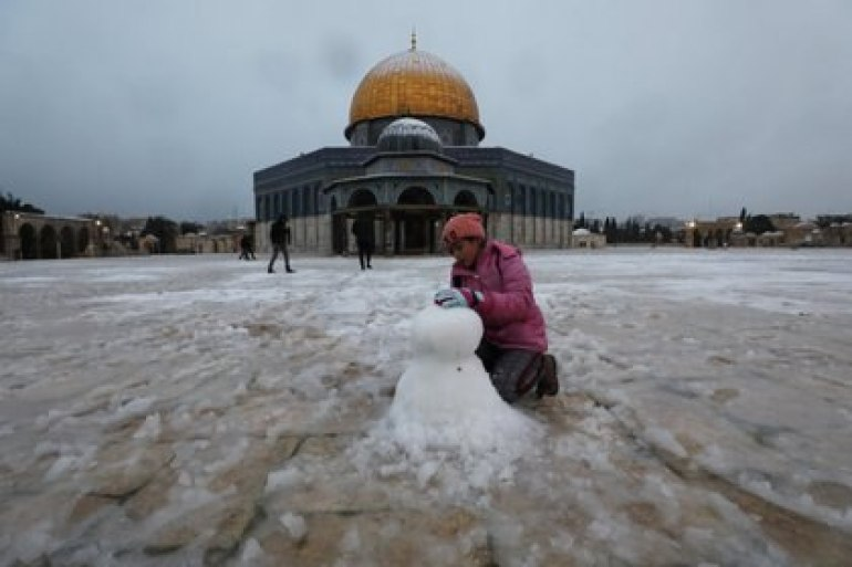 A girl plays next to the Dome of the Rock in the complex known to Jews as the Temple Mount and Muslims as the Noble Sanctuary on a snowy morning in the Old City of Jerusalem on February 18, 2021. REUTERS / Ammar awad