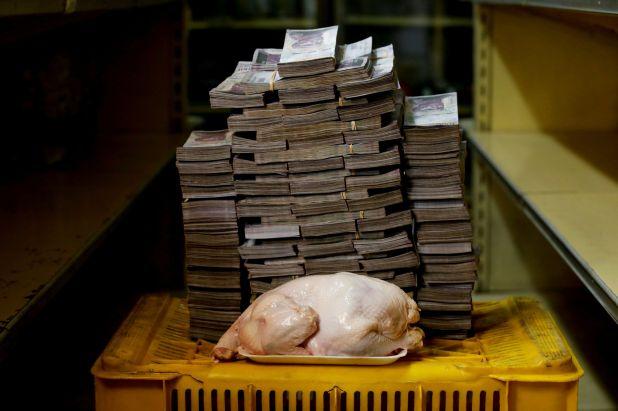 Un pollo de 2,4 kg es fotografiado junto a 14.600.000 bolívares, su precio y el equivalente a 2,22 USD, en un mini-mercado en Caracas, Venezuela, el 16 de agosto de 2018 (REUTERS/Carlos Garcia Rawlins)