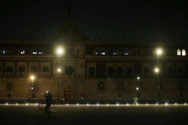 Un hombre toma fotos durante la noche frente al Palacio Nacional en Ciudad de México, México (Foto: REUTERS/Edgard Garrido)