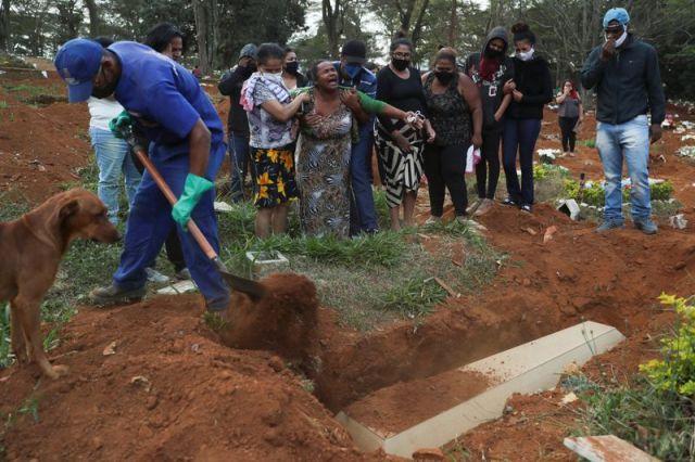 Los familiares reaccionan durante el entierro de Raimunda Conceicao Souza, de 64 años, quien murió a causa de la enfermedad por coronavirus (COVID-19), en el cementerio de Vila Formosa, el más grande de Brasil, en Sao Paulo.