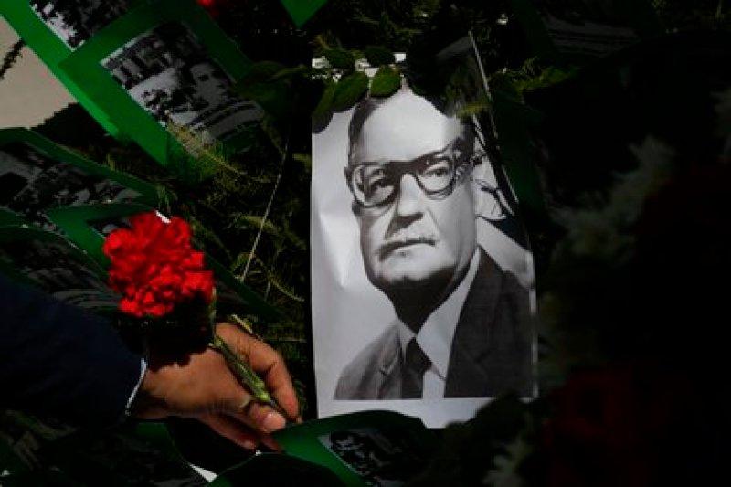 Un hombre deja una flor sobre la imagen del presidente chileno Salvador Allende, este viernes en Santiago. EFE/Elvis González