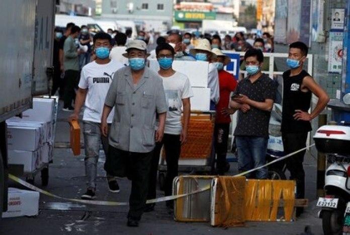 Varios hombres con mascarillas en el interior del mercado de marisco Jingshen, cerrado al comercio tras la detección de nuevas infecciones por coronavirus, en Pekín, China, el 12 de junio de 2020. REUTERS/Thomas Peter