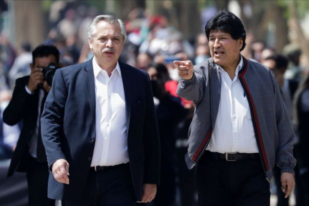 Former Bolivian President Evo Morales, next to Argentina's President Alberto Fernandez, walks over a bridge while returning to his home country from exile in Argentina, at the border town of Villazon, Bolivia, November 9, 2020. REUTERS/Ueslei Marcelino