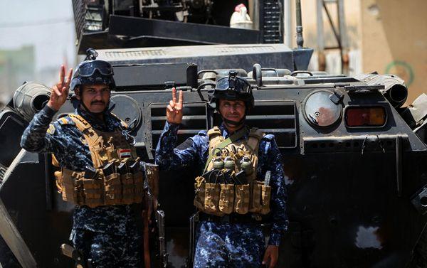 Miembros de la policía mostrando su buen espíritu. Los iraquíes se sienten al borde de la victoria a pesar de que el ISIS logró preocupantes infiltraciones en sus líneas (AFP)