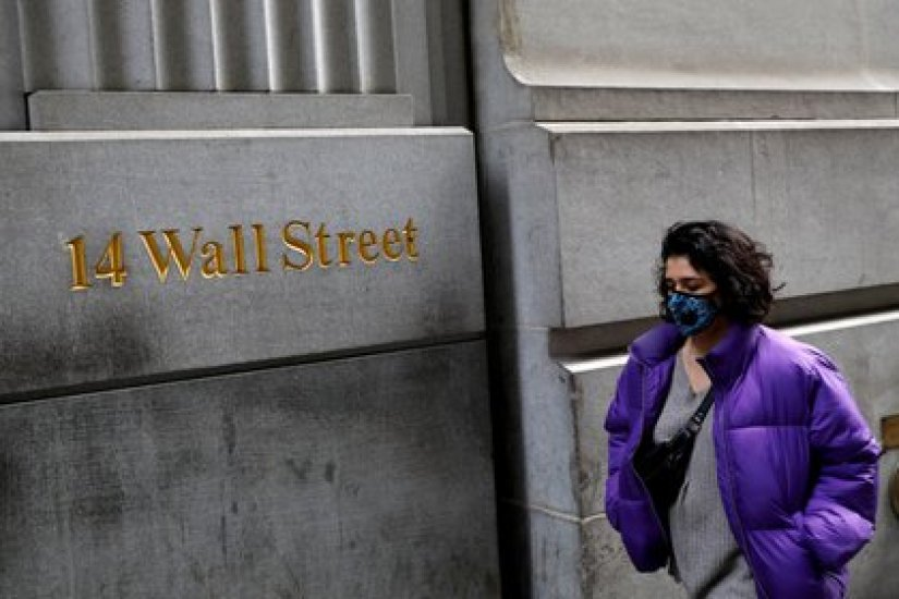 A person wearing a face mask walks down Wall Street after more cases of coronavirus were confirmed in New York City, New York, USA, on March 6, 2020.