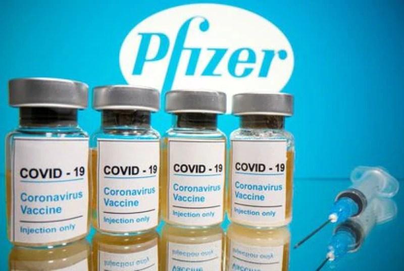 Viales y una jeringa médica frente al logotipo de Pfizer
