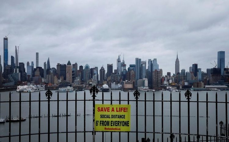 Un cartel que promueve el distanciamiento social cuelga de una valla en Hamilton Park, sobre el río Hudson, con el horizonte de la ciudad de Nueva York de Manhattan al fondo, durante el brote de la enfermedad coronavirus (COVID-19), desde Weehawken, Nueva Jersey, EEUU, el 3 de abril, 2020. REUTERS/Mike Segar