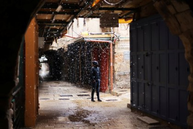 A man watches snow fall in an alley in Jerusalem's Old City on February 17, 2021. REUTERS / Ammar Awad