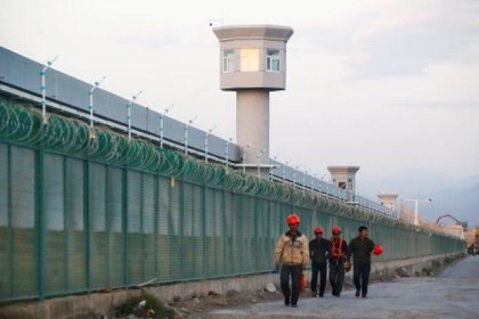 Trabajadores caminan por el perímetro de lo que el régimen chino llama campo de educación vocacional, pero que es ampliamente considerado como un campo de concentración y trabajo forzado para miembros de la minoría Uigur. Foto: REUTERS/Thomas Peter