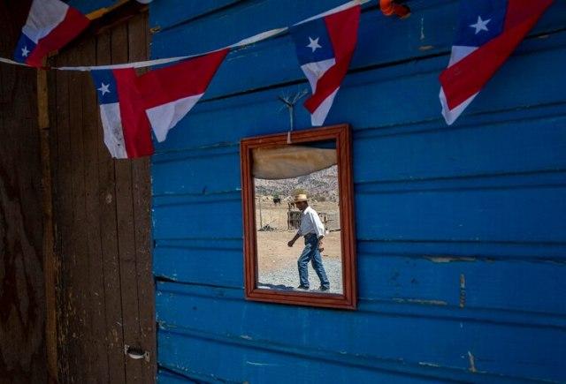El ganadero Benito Morena se refleja mientras camina en un espejo de su rancho. Desde la región de Coquimbo en el norte de Chile hasta Maule en el sur, más de 30.000 cabezas de ganado han muerto por hambre o sed, y los cultivos se han perdido por falta de lluvias, de acuerdo con el Ministerio de Agricultura