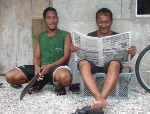 Rivel Line sits with Brian Tabto, who is enjoying reading the Marshall Islands Journal.