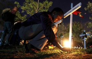 "A woman lights a candle on a wooden cross after a memorial concert for the Garissa university students who were killed during an attack by gunmen, at the ""Freedom Corner"" in Kenya's capital Nairobi April 14, 2015. REUTERS/Thomas Mukoya"