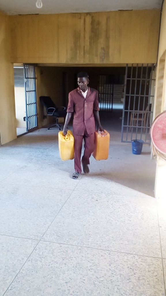 A cleaner carrying two jerry-cans to supply water to toilet on first floor of Office of Accountant-General, Ogun state secretariat