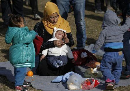 70 Migrants woman holds a child at a migrant center near the village of Adasevci