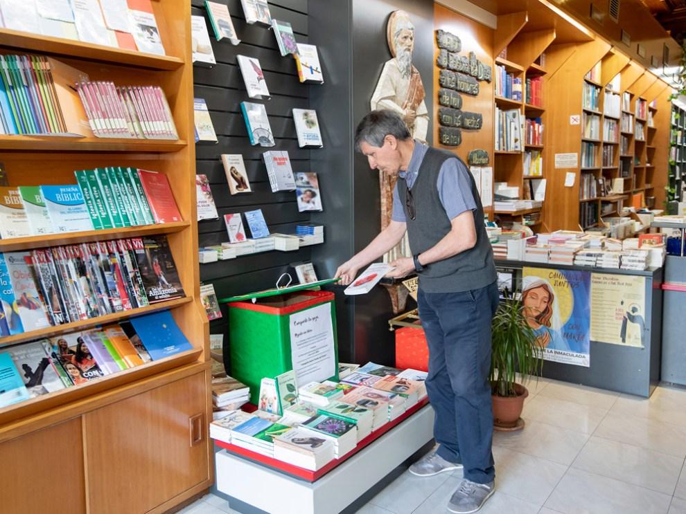Uno de los capellanes de hospital junto a la caja donde se depositan los libros de la campaña, en la librería Paulinas de Valencia./Víctor Gutiérrez