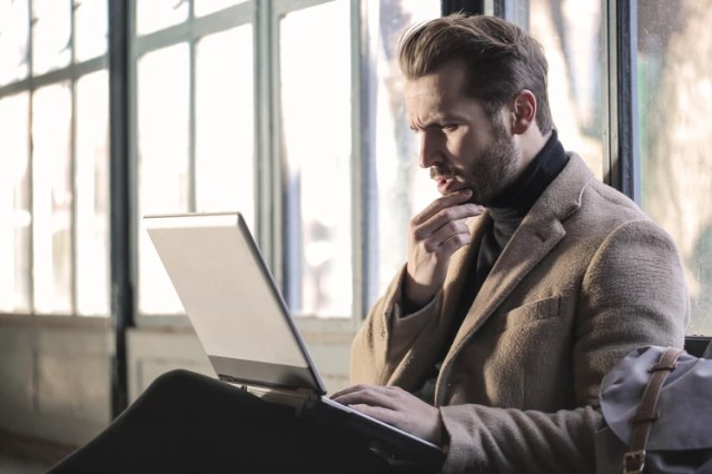 homem desconfiado olhando para o computador - Dicas para ficar de olho antes de Comprar On-line.