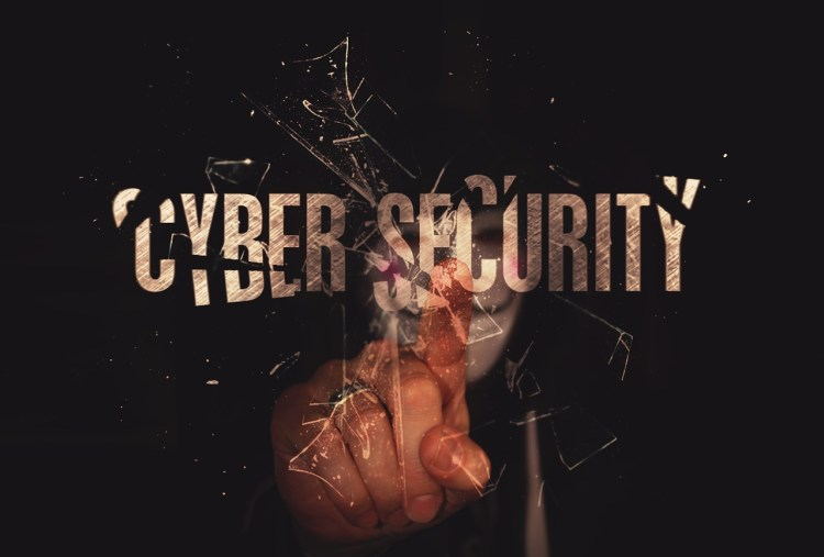 A color photo of a man pointing at an inscription Cyber Security – used to illustrate a point about importance of cyber security awareness