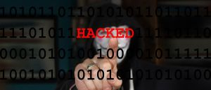 Color photo of an anonymous person in the background, pointing at the word HACKED.