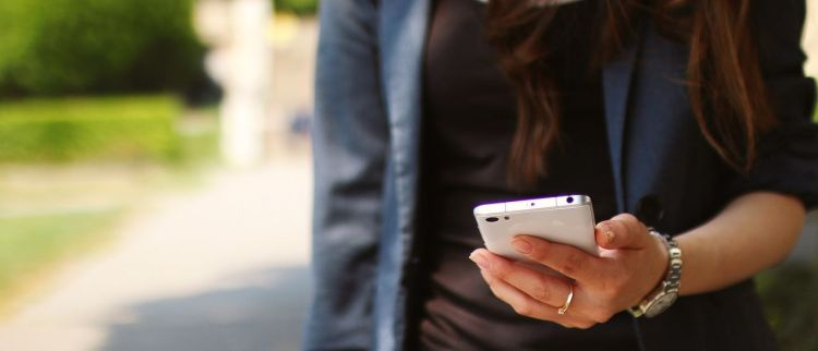 Color photo of a woman walking and holding a smartphone.