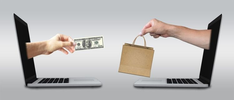 Color photo of two laptops, with onscreen hand exchanging a paper bag and 100 dollar bill - used to illustrate the importance of safe online shopping and banking.