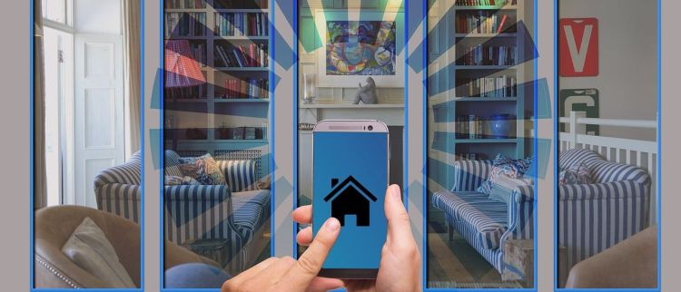 Color photo of a smartphone with a living room in the background; used to illustrate the meaning of IoT Security at home.