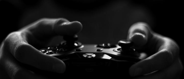 Color photo of human hands holding a gaming controller used to illustrate the importance of gaming safety.