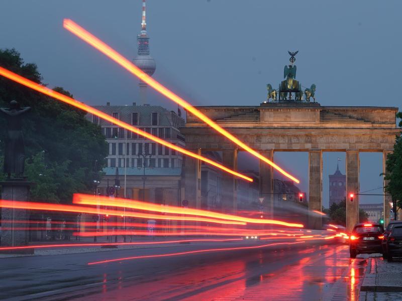 Durch eine Langzeitbelichtung sind die Rückleuchten eines Busses vor dem Brandenburger Tor als Linien zu sehen. Foto: Jörg Carstensen/dpa